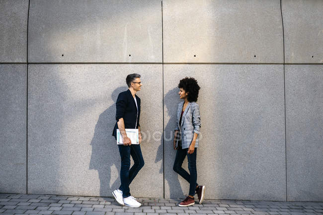 Two colleagues talking outdoors leaning against a wall — Stock Photo