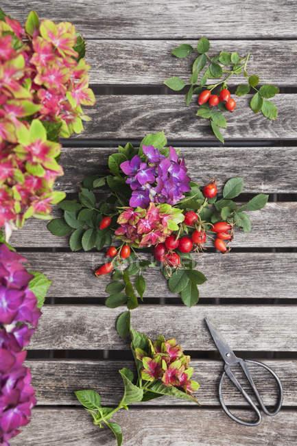 Hortênsias, roseiras e tesouras na mesa de jardim — Fotografia de Stock
