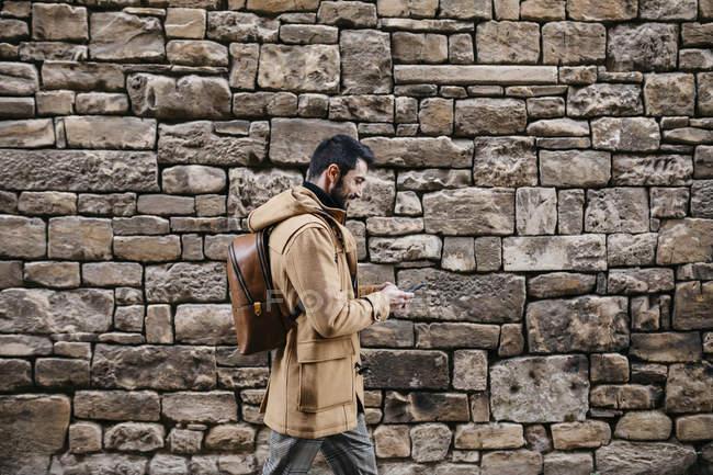 Espanha, Igualada, homem andando ao longo da parede de pedra usando telefone celular — Fotografia de Stock