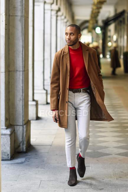 Joven de moda con jersey rojo y abrigo marrón caminando a lo largo de arcade - foto de stock