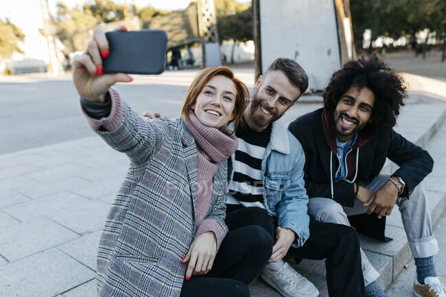 Three happy friends sitting outdoors taking a selfie — Stock Photo