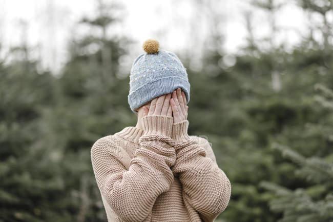 Мальчик в шерстяной шапке, закрывающей лицо — стоковое фото