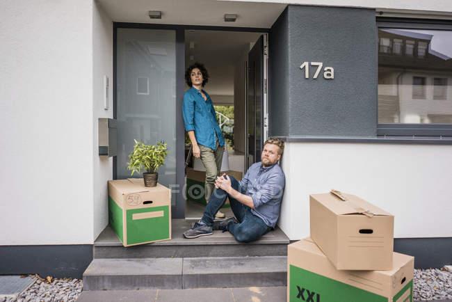 Coppia all'ingresso della casa con scatole di cartone — Foto stock