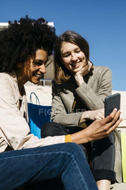 Две счастливые женщины с сумками для покупок сидят на улице с мобильным телефоном — стоковое фото