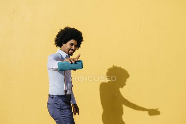 Smiling man with loudspeaker listening music and dancing in front of yellow wall — Stock Photo
