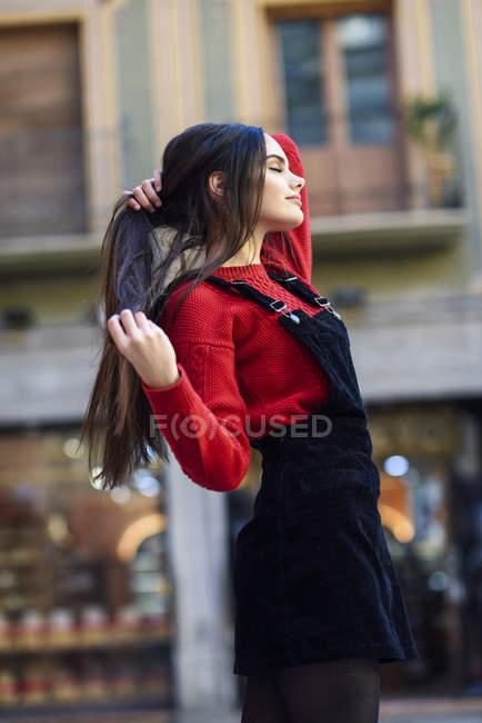 Модная молодая женщина в красном пуловере и черном платье из бретелек в городе — стоковое фото