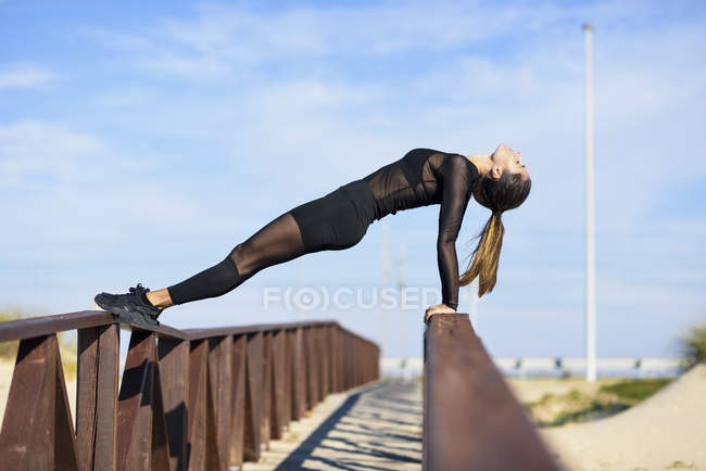 Спортивная женщина на перилах деревянного моста — стоковое фото