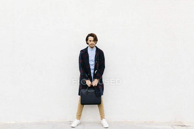 Ritratto di uomo sicuro di sé con una valigetta appoggiata a un muro — Foto stock