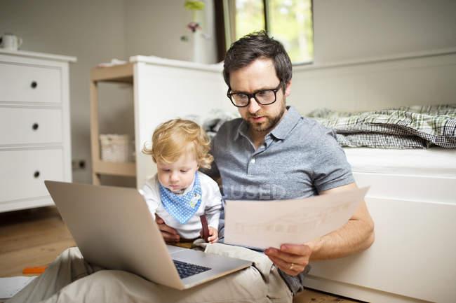Батько зі своїм маленьким сином працює на дому — стокове фото