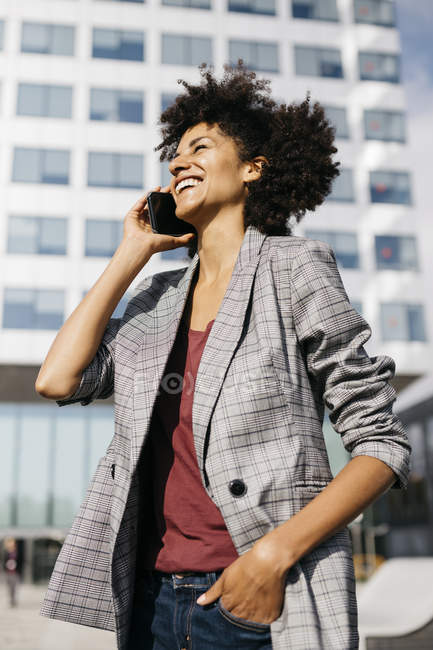 Laughing businesswoman on cell phone outside office building — Stock Photo