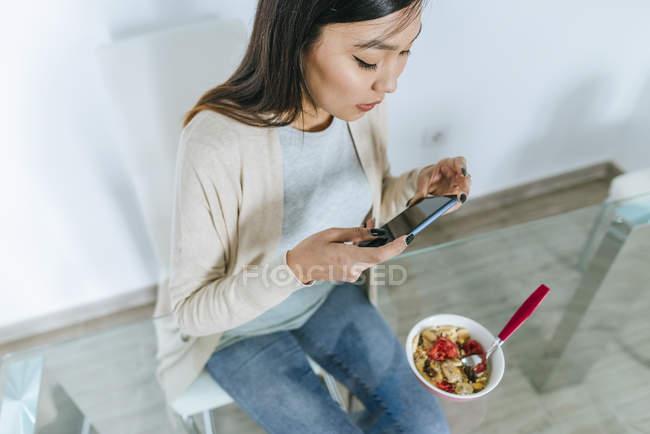 Junge Frau isst Müsli zum Frühstück, während sie das Smartphone benutzt — Stockfoto