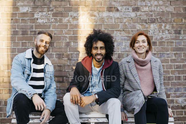 Retrato de três amigos felizes sentados em um banco na frente de uma parede de tijolo — Fotografia de Stock