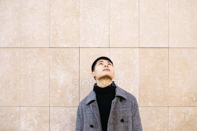 Молодий чоловік у перукарні та пальто, що дивляться вгору. — стокове фото