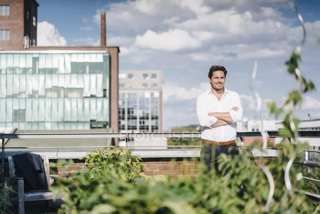 Geschäftsmann baut Pflanzen in seinem städtischen Dachgarten an — Stockfoto