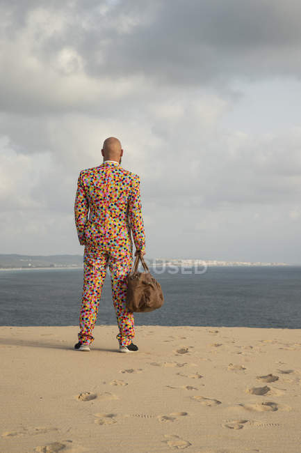 Back view of man with travelling bag wearing suit with colourful polka-dots standing on sand dune — Stock Photo