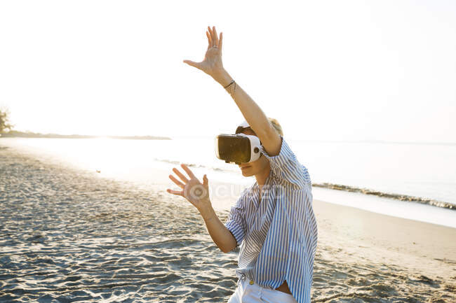 Thailand, woman using virtual reality glasses on the beach in the morning light — Stock Photo