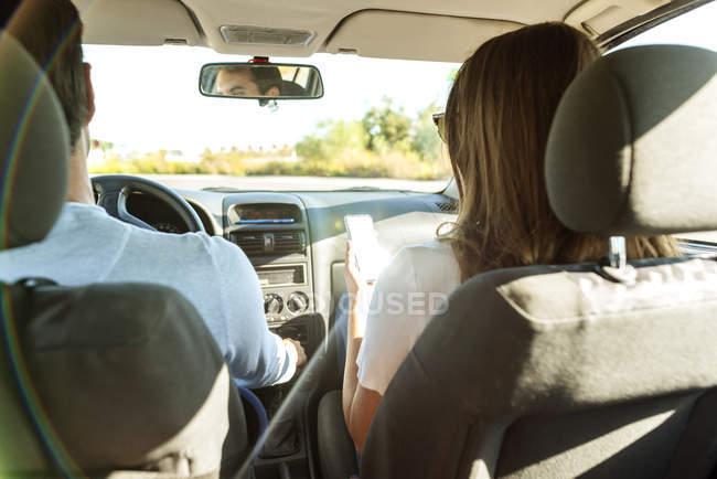 Pareja conduciendo en coche con la mujer en el asiento del pasajero usando el teléfono celular - foto de stock