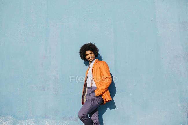 Retrato de un hombre elegante inclinado contra la pared azul - foto de stock