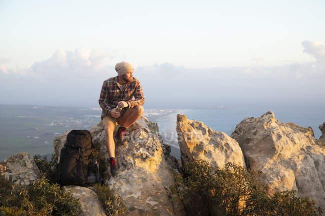 Іспанія, Андалусія, Таріфа, людина, яка подорожувала узбережжям, сидячи на скелі. — стокове фото