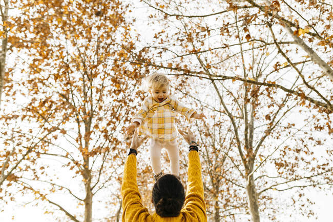 Father throwing his daughter in air, in a park in autumn — Stock Photo
