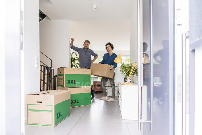 Portrait of couple in new home with cardboard boxes — Stock Photo