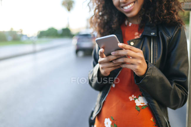 Donna in piedi sul ciglio della strada con smartphone, primo piano — Foto stock