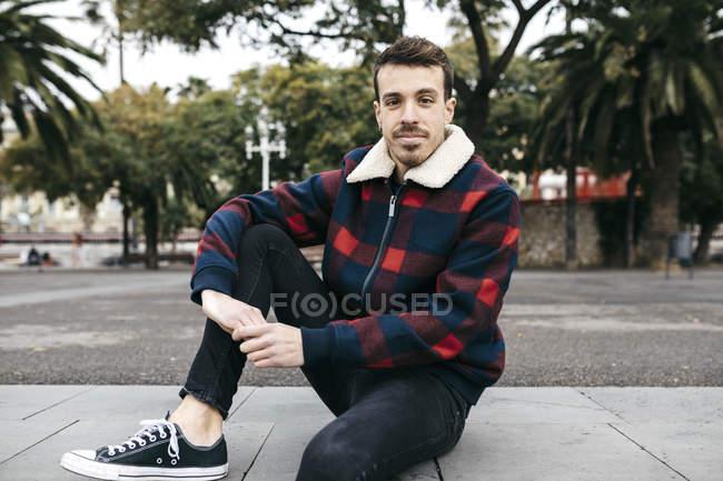 Junger Mann in legerer Kleidung sitzt auf einer Bank in der Stadt — Stockfoto