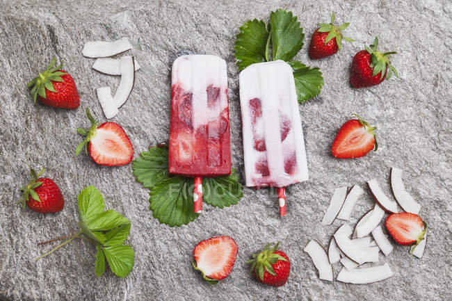 Homemade strawberry coconut ice lollies with fresh strawberries and coconut slices on granite — Stock Photo