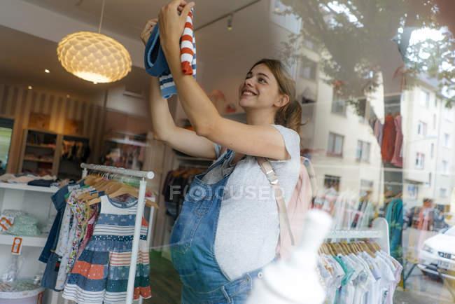 Улыбающаяся беременная женщина покупает детскую одежду в бутике — стоковое фото