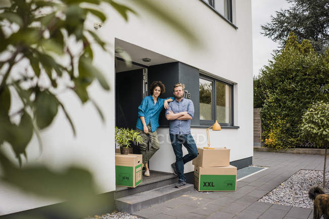 Couple standing at house entrance with cardboard boxes — Stock Photo