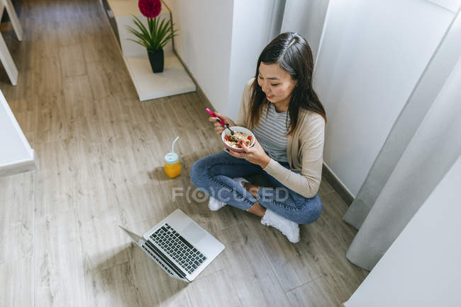 Young woman sitting on floor, using smartphone — Stock Photo