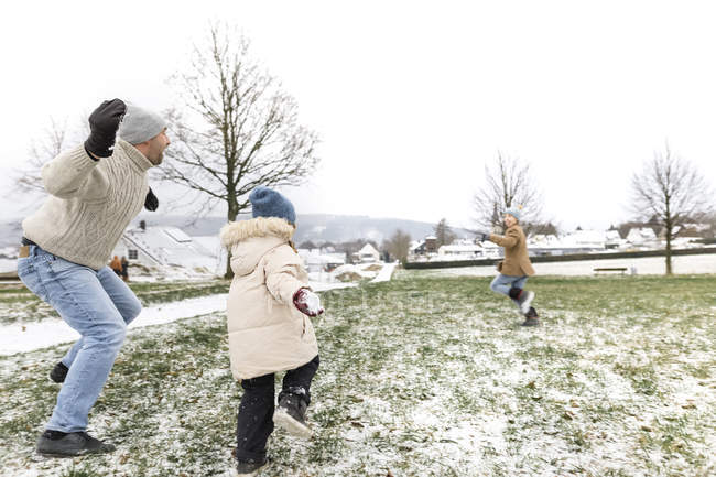 Padre y dos hijos teniendo una pelea de bolas de nieve - foto de stock