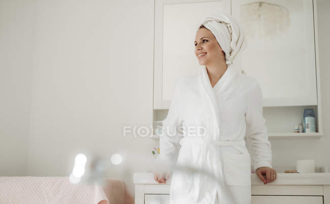 Улыбающаяся женщина в халате с игрушкой на голове стоит дома в ванной — стоковое фото