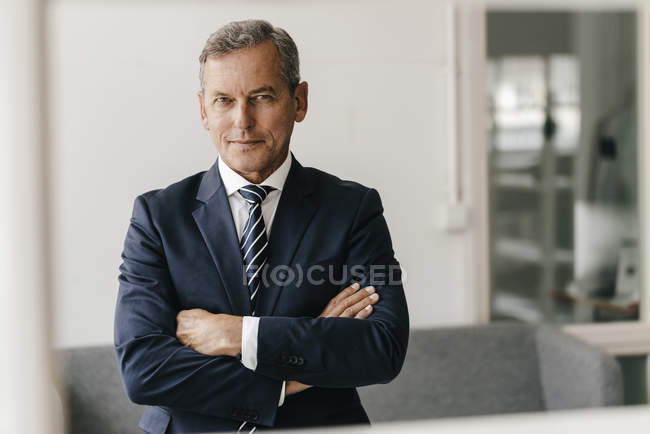 Portrait of mature businessman with arms crossed in his office — Stock Photo