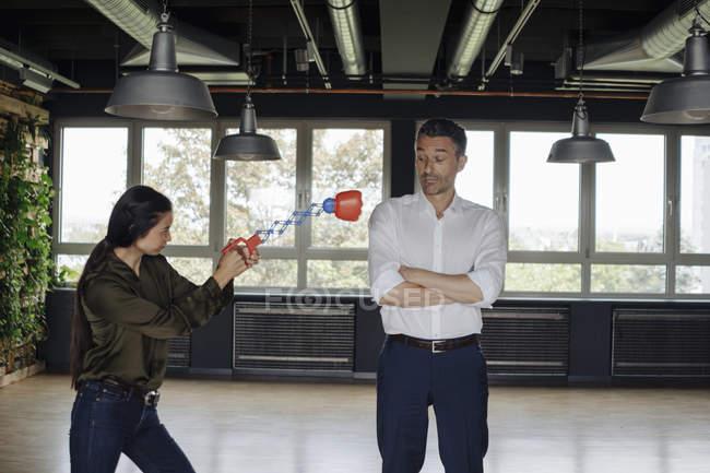 Femme d'affaires dans le bureau frappant l'homme d'affaires avec le jouet de boxe — Photo de stock