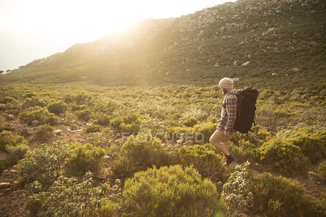 Espanha, Andaluzia, Tarifa, homem em uma viagem de caminhada caminhando em uma trilha na luz do fundo — Fotografia de Stock