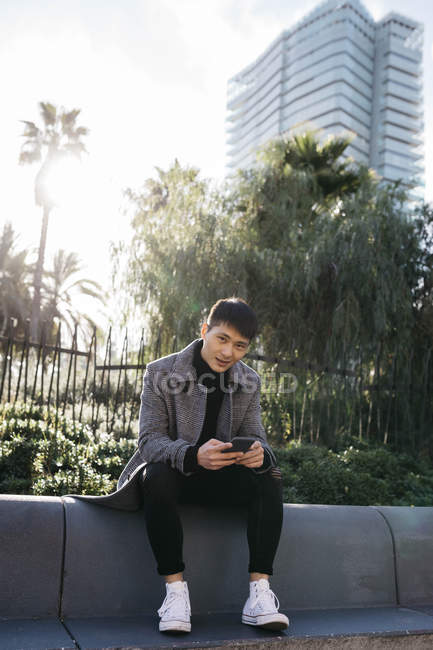 Spain, Barcelona, portrait of young man with mobile phone sitting on a wall — Stock Photo