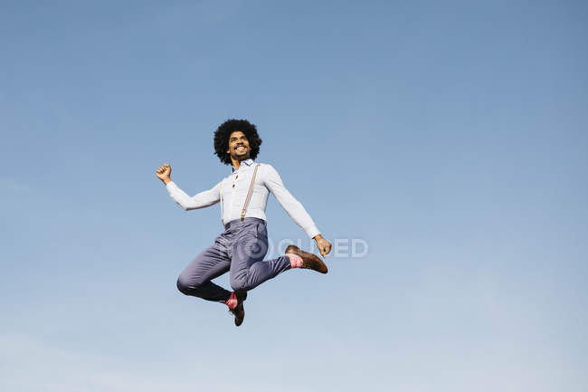 Smiling man jumping in the air against blue sky — Photo de stock