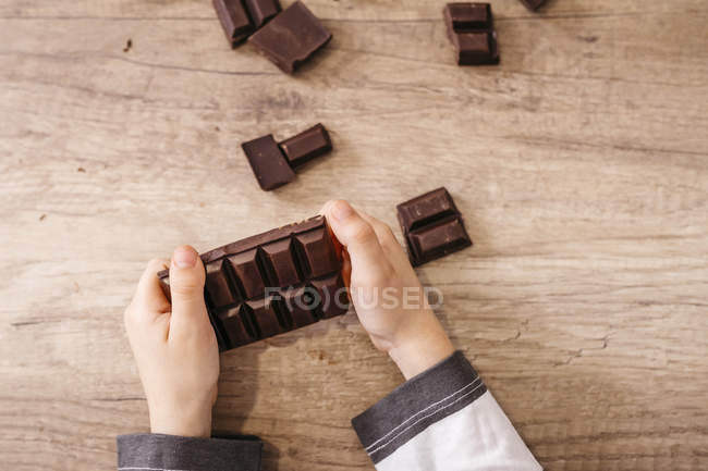 Mãos do menino que prendem a barra de chocolate, close-up — Fotografia de Stock