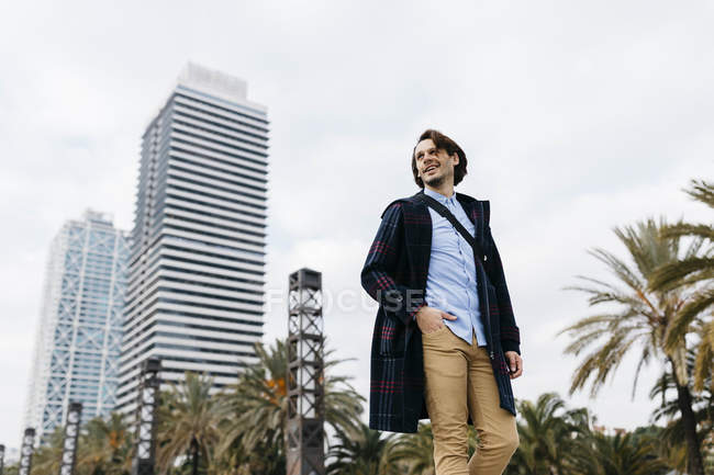 Spain, Barcelona, smiling man walking in the city with two skyscrapers in the background — Stock Photo