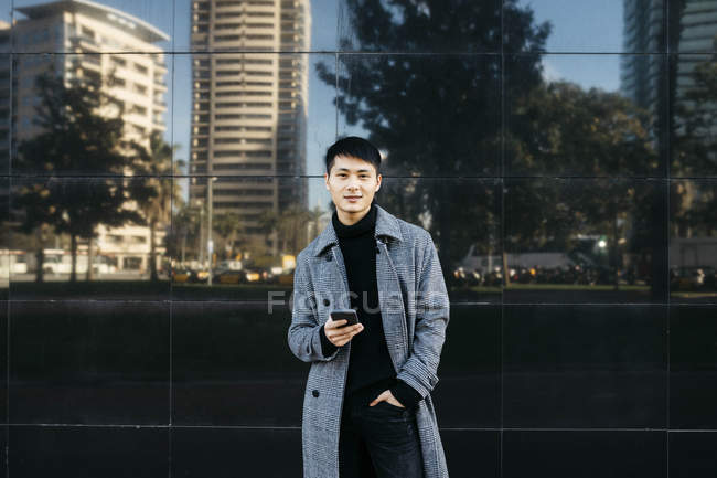 Spain, Barcelona, portrait of young man with cell phone wearing black turtleneck pullover and grey coat - foto de stock