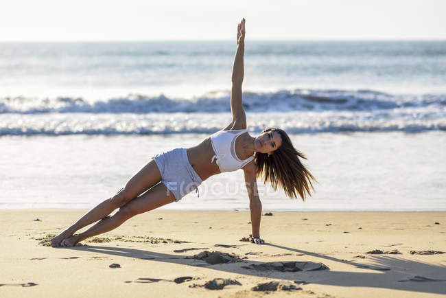 Спортивная женщина, занимающаяся на пляже — стоковое фото
