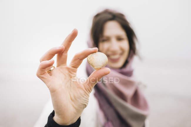 La mano de la mujer sosteniendo la cáscara recogida, primer plano - foto de stock