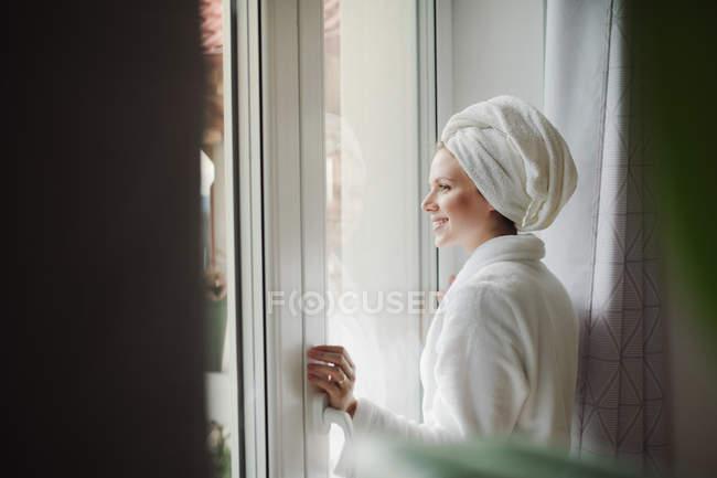 Улыбающаяся женщина в халате с игрушкой на голове, выглядывающая из окна дома — стоковое фото
