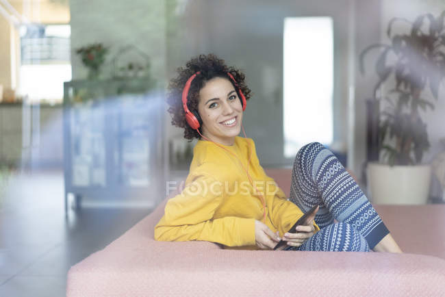 Happy woman listening to music on couch at home — Stock Photo