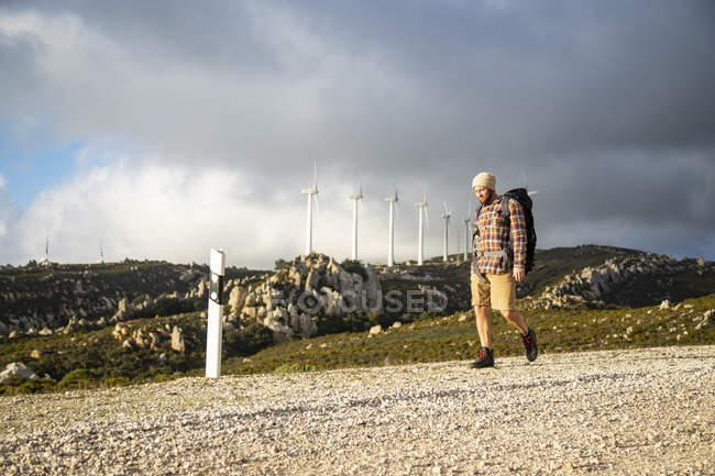 Spain, Andalusia, Tarifa, man on a hiking trip walking on dirt road with wind turbines in background — Stock Photo