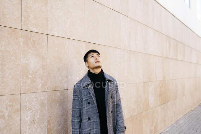 Молодий чоловік у перукарні і сірому пальто, дивлячись вгору. — стокове фото