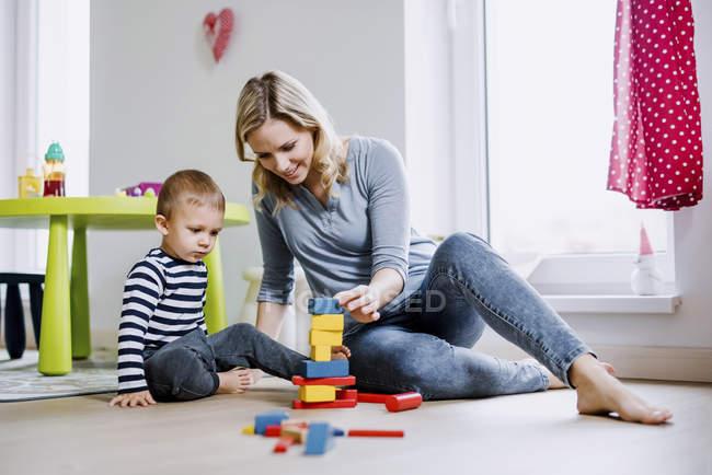 Sonriente madre e hijo pequeño jugando con bloques de construcción en casa - foto de stock