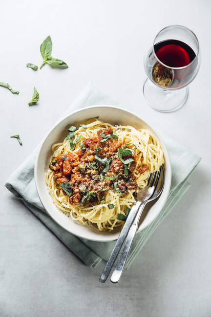 Spaghetti with tomato caper sauce, basil and parmesan with a glass of red wine — Stock Photo