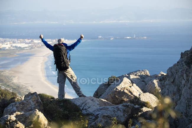 Spain, Andalusia, Tarifa, man on a hiking trip at the coast looking at view cheering — Stock Photo